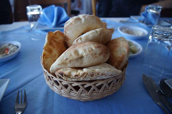 類似口袋餅的麵包,撕開後夾入白色的鷹豆泥醬,左手邊的小盤子,看見了嗎?