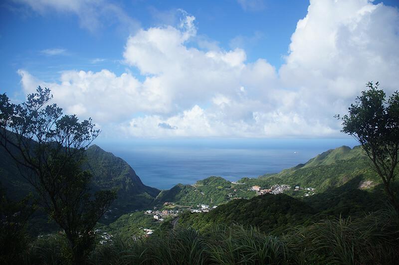 山線彷彿倒了大大小小的圓角,海天連成一線,靠雲朵來分界。